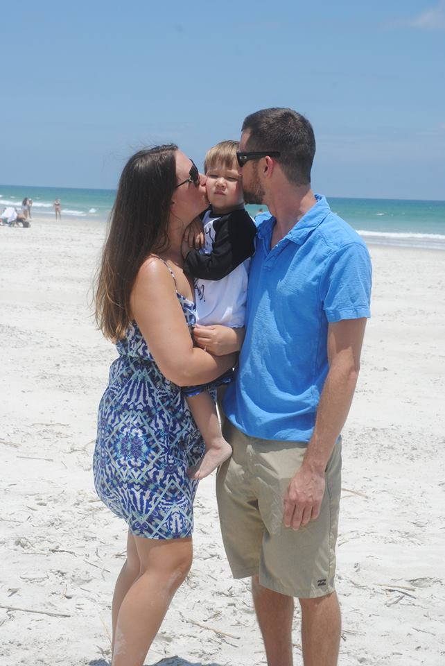 mom and dad kissing toddler on cheeks